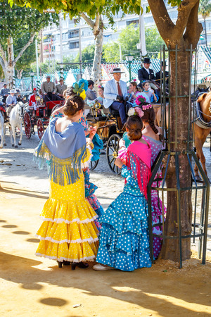 Seville, Spain - May 03, 2017:  Young Women relaxing and dressed in traditional costumes at the Seville's April Fair. Foto de archivo - 97410239