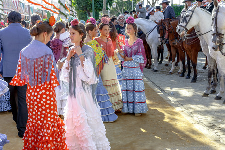 Seville, Spain - May 03, 2017:  Young Women relaxing and dressed in traditional costumes at the Seville's April Fair. Foto de archivo - 97410278
