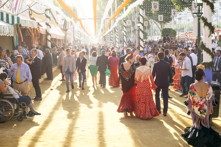 Seville, Spain - May 03, 2017:  People taking a walk at sunset, having fun and dressed in traditional costumes at the Seville's April Fair. Foto de archivo - 97410414