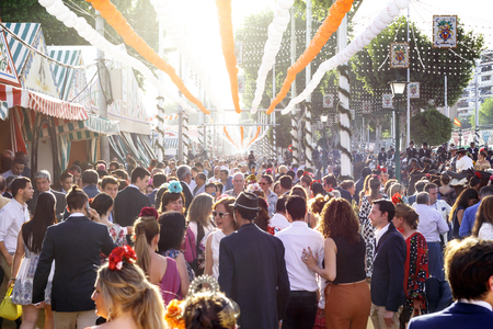 Seville, Spain - May 03, 2017: Crowd of people of all ages having fun at sunset and dressed in traditional costumes at the Seville's April Fair. Foto de archivo - 97410417