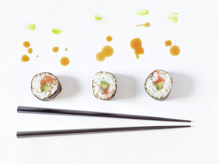 Sushi rolls and chopsticks with splashes of soy sauce and brush strokes of wasabi. Concept design.  Japanese cuisine.