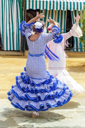 Seville, Spain - May 04, 2017:  Women dressed in colourful flamenco dresses and dancing at the Seville April Fair. The Feria de Abril has a history that dates back to 1857 and takes place a fortnight after Easter each year. The origin of the fair was a ca Foto de archivo - 108846196