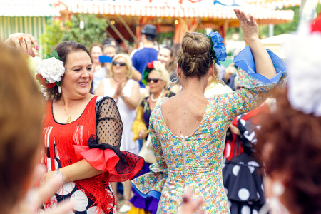 Seville, Spain - May 04, 2017:  Women wearing traditional Sevillana dresses and dancing a Sevillana at the Seville April Fair. The Feria de Abril has a history that dates back to 1857 and takes place a fortnight after Easter each year. The origin of the f Foto de archivo - 108846197