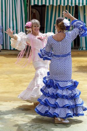 Seville, Spain - May 04, 2017:  Women dressed in colourful flamenco dresses and dancing at the Seville April Fair. The Feria de Abril has a history that dates back to 1857 and takes place a fortnight after Easter each year. The origin of the fair was a ca Foto de archivo - 108846199