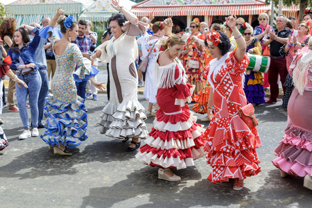Seville, Spain - May 04, 2017:  Women wearing traditional Sevillana dresses and dancing a Sevillana at the Seville April Fair. The Feria de Abril has a history that dates back to 1857 and takes place a fortnight after Easter each year. The origin of the f
