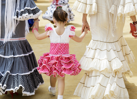 Family in traditional dress taking a walk and enjoying at the Seville's April Fair. Foto de archivo - 98150670