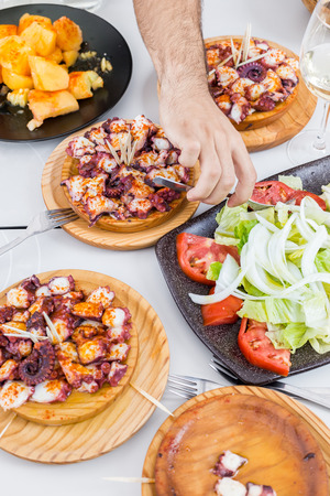 Male hand eating vegetable salad and galician style cooked octopus with paprika and olive oil. Pulpo a la gallega