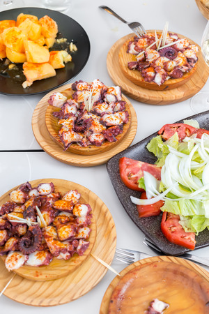 Vegetable salad, potatoes and galician style cooked octopus with paprika and olive oil. Pulpo a la gallega Standard-Bild