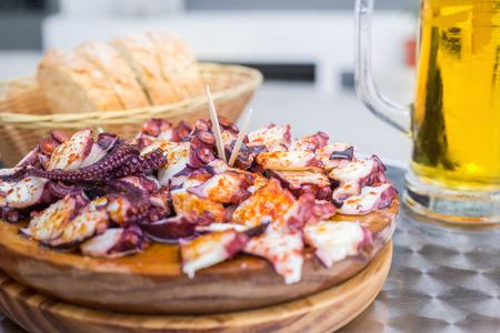Gustoso piatto in legno di polpo cotto in stile galiziano con paprika e olio d'oliva. Pulpo a la gallega.