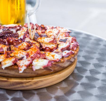 Delicious Wooden plate of galician style cooked octopus and Glass of cold beer . Pulpo a la gallega