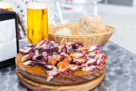 Cold beer and Wooden plate of galician style cooked octopus with paprika and olive oil. Pulpo a la gallega