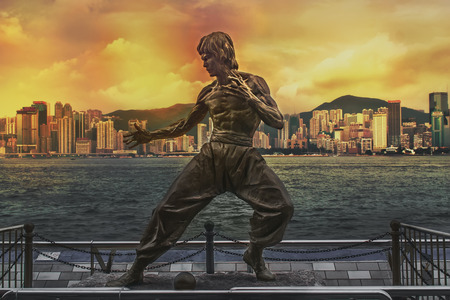 Hong Kong, China - July 20, 2010: Bruce Lee statue at the Avenue of Stars. Skyline over Victoria Harbour in the background at sunset. The Bruce Lee statue in Hong Kong is a memorial figure of deceased martial artist, Bruce Lee.