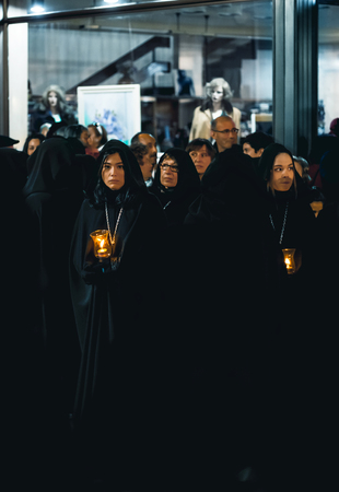 Zamora, Spain - March 31, 2018: Ladies of the Virgin of Solitude during holy week (semana santa) in Zamora, Spain. The ladies wear rigorous mourning, with a black cloak with a cap, with a distinctive medal and with a glass tulip.