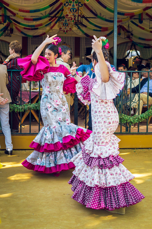 Sevilla, Spain - April 18, 2018: Young women wearing flamenco dresses and dancing