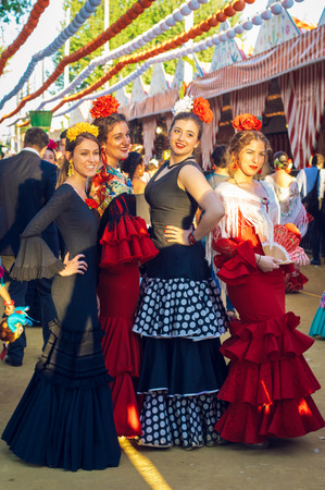 """Sevilla, Spain - April 18, 2018: Beautiful women in traditional and colorful dress enjoy April Fair, Seville Fair (Feria de Sevilla). The Seville Fair (officially and in Spanish: Feria de abril de Sevilla, """"Seville April Fair"""") is held in Andalusian capit"""
