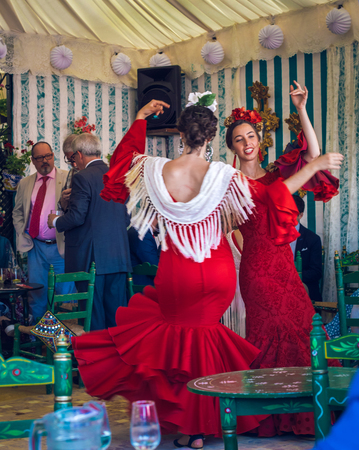 Sevilla, Spain - April 18, 2018: Young and beautiful women wearing flamenco dresses and dancing