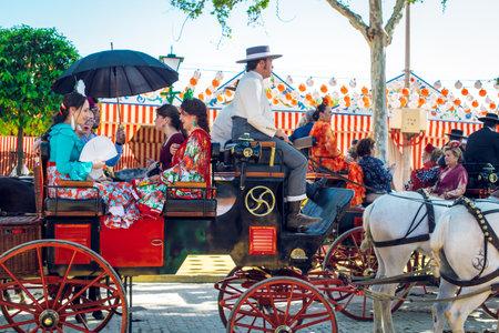 """Sevilla, Spagna - 18 aprile 2018: Famiglie spagnole in abito tradizionale che viaggiano in carrozze trainate da cavalli alla Fiera di aprile, Fiera di Siviglia (Feria de Sevilla). La Fiera di Siviglia (ufficialmente e in spagnolo: Feria de abril de Sevilla, """"Fiera di aprile di Siviglia"""")"""