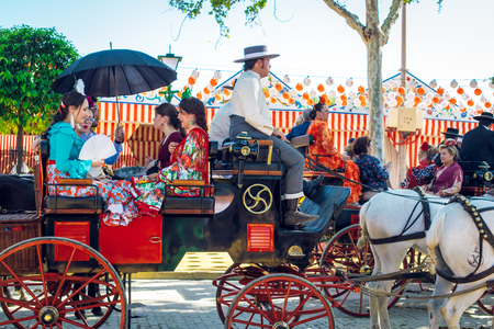 "Sevilla, Spain - April 18, 2018: Spanish families in traditional dress travelling in a horse drawn carriages at the April Fair, Seville Fair (Feria de Sevilla). The Seville Fair (officially and in Spanish: Feria de abril de Sevilla, ""Seville April Fair"")"