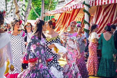 "Sevilla, Spain - April 18, 2018: Beautiful women dressed in traditional costumes enjoy April Fair , Seville Fair (Feria de Sevilla). The Seville Fair (officially and in Spanish: Feria de abril de Sevilla, ""Seville April Fair"") is held in Andalusian capita Editorial"
