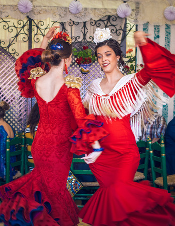 "Sevilla, Spain - April 18, 2018: Young and beautiful women wearing flamenco dresses and dancing ""Sevillanas"" at the April Fair, Seville Fair (Feria de Sevilla). The Seville Fair (officially and in Spanish: Feria de abril de Sevilla, ""Seville April Fair"") Editorial"