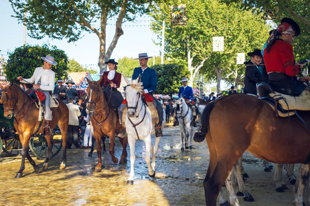 Sevilla, Spain - April 18, 2018: Horse drawn carriages and riders at the April Fair, Seville Fair (Feria de Sevilla). The Seville Fair (officially and in Spanish: Feria de abril de Sevilla,