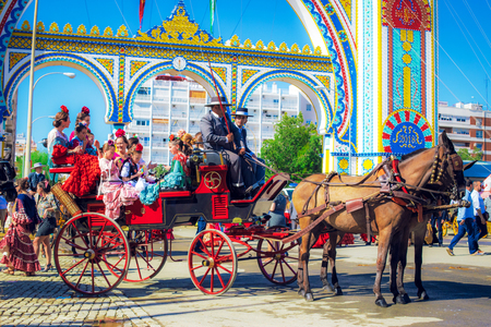 """Sevilla, Spain - April 18, 2018: Spanish families in traditional and colorful dress travelling in a horse drawn carriages at the April Fair, Seville Fair (Feria de Sevilla). The Seville Fair (officially and in Spanish: Feria de abril de Sevilla, """"Seville"""