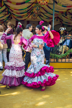 """Sevilla, Spain - April 18, 2018: Young women wearing flamenco dresses and dancing """"Sevillanas"""" at the April Fair, Seville Fair (Feria de Sevilla). The Seville Fair (officially and in Spanish: Feria de abril de Sevilla, """"Seville April Fair"""") is held in And Editorial"""