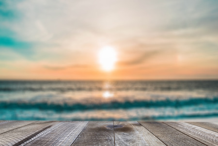 Top of wood table with blurred sea and sunset. Standard-Bild - 120541133