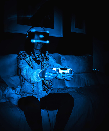 Woman with virtual reality headset sitting on the couch at home. Standard-Bild - 123093795
