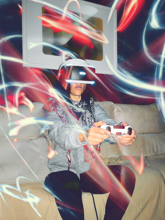Woman with virtual reality headset sitting on the couch at home. Standard-Bild - 123093793