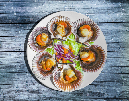Grilled Galician Scallops with salad on bluewooden table. Standard-Bild - 124096732