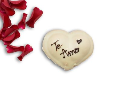 Festive dessert in the shape of a heart with text I love you in Spanish and rose petals isolated on white.