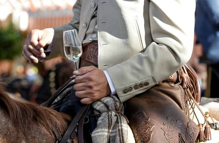 Rider on horseback dressed in traditional costume and holding glass of fino sherry (manzanilla sherry) at the April Fair (Feria de Abril), Seville Fair (Feria de Sevilla), Andalusia, Spain. Travel and tourism concepts