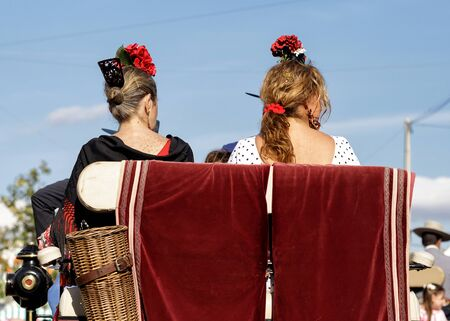 Women dressed in traditional costumes on a horse drawn carriage at the April Fair (Feria de Abril), Seville Fair (Feria de Sevilla), Andalusia, Spain Stock Photo