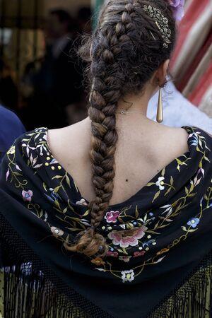 Beautiful woman wearing flamenco dress. Detail of Traditional Spanish Hairstyleat the April Fair (Feria de Abril), Seville Fair (Feria de Sevilla), Andalusia, Spain. Spanish folklore
