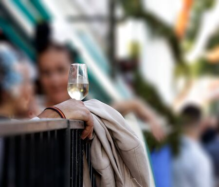 Hand holding glass of fino sherry (manzanilla sherry) at the April Fair (Feria de Abril), Seville Fair (Feria de Sevilla), Andalusia, Spain. Travel and tourism concepts. Selective focus.