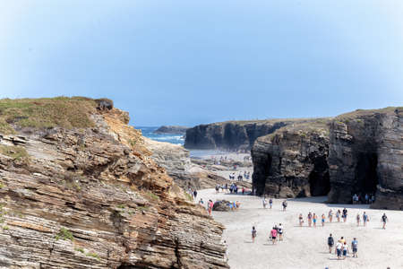 Ribadeo, Spain - August 21 2019: Cathedrals beach. Designated a Natural Monument, is one of the most famous beaches in Galicia. It is known around the world for its rocky formations carved by the wind and sea.