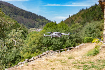 Quadcopter drone with digital camera in flight with landscape and blue sky background. Stock Photo - 151718858