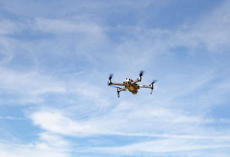 Quadcopter drone with digital camera in flight with blue sky background