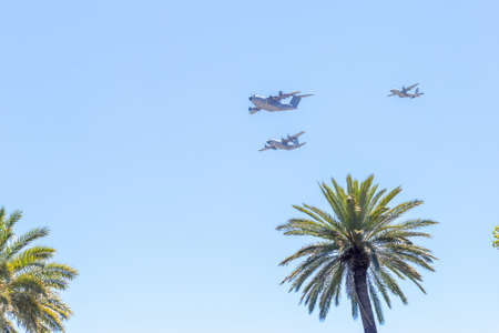 Modern armed military transport planes flys in formation through the sky.