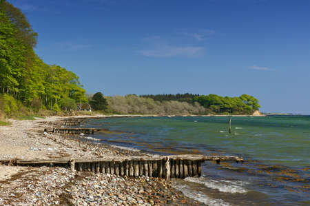 quite: Baltic seashore with beach, anchored boat, breakwater and wooded cliff Stock Photo