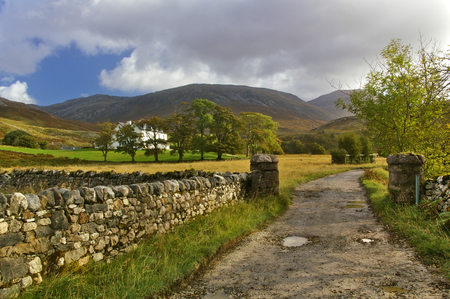 Gravel road leading through two gateposts beside a fieldstone wall towards a distant mountain range Stock Photo