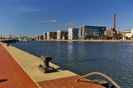 Harbour view with red brick quay and bollard in the foreground and office buildings and construction sites in the background Stock Photo