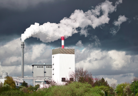 Hydroelectric power plant emitting white steam in front of a dark grey rain cloud Stock Photo