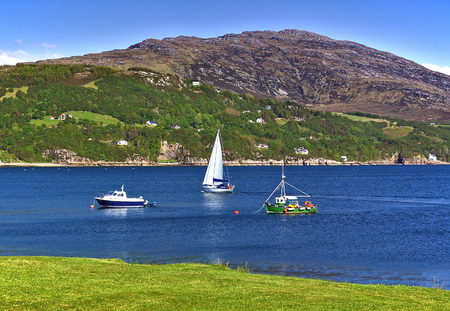 Sailing yacht and fishing boats with mountain range in the background and green grassy seashore in the foreground