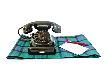 Vintage telephone on tartan plaid with red pen and notepad with copyspace isolated on white background