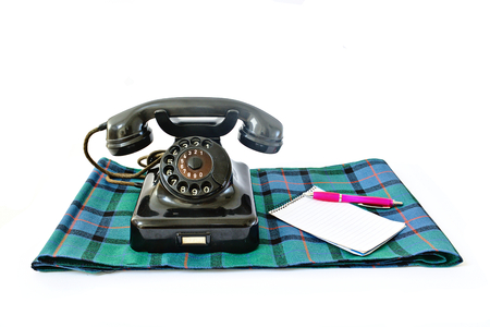 Vintage telephone on tartan plaid with pink pen and notepad with copyspace isolated on white background