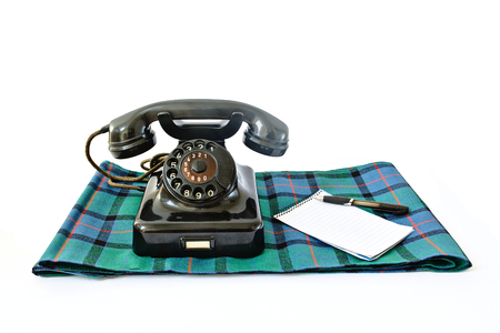 caller: Vintage telephone on tartan plaid with black pen and notepad with copyspace isolated on white background Stock Photo