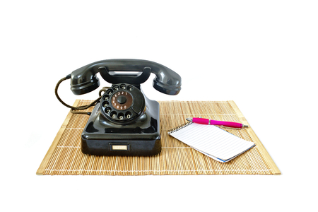 caller: Vintage telephone on rattan mat with pink pen and notepad with copyspace isolated on white background