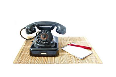 caller: Vintage telephone on rattan mat with red pen and notepad with copyspace isolated on white background